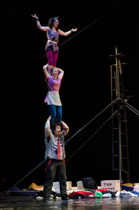 A female performer stands on the shoulder of a male performer, with another female acrobat standing on her shoulder