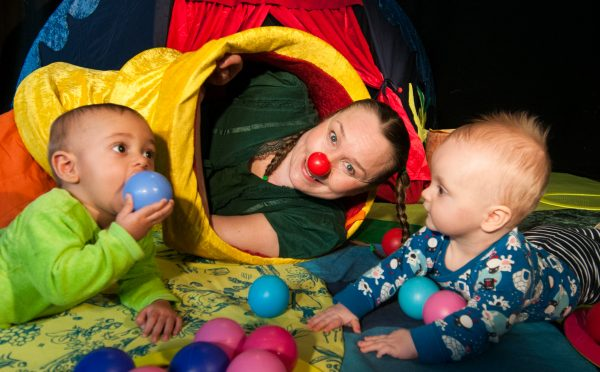Woman in red nose pokes her head out from a fabric tunnel, as two babies play next to her